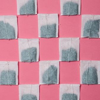 Patroon van witte theezakje op roze achtergrond