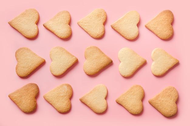 Patroon van zelfgemaakte traditionele hartvormige koekjes voor valentijnsdag op roze
