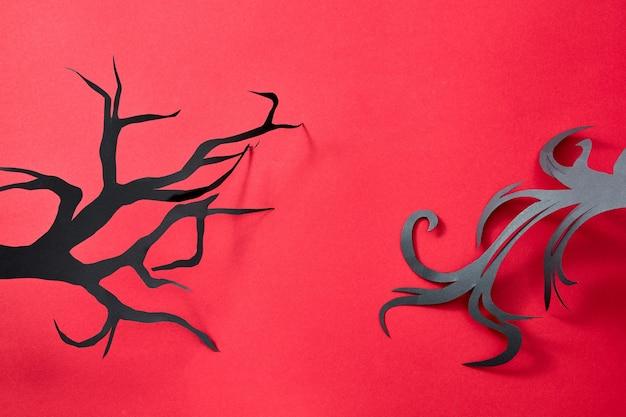 Patroon van zwarte handgemaakte papieren boomtakken op een rode achtergrond met ruimte voor tekst. mystieke halloween-briefkaart. plat leggen
