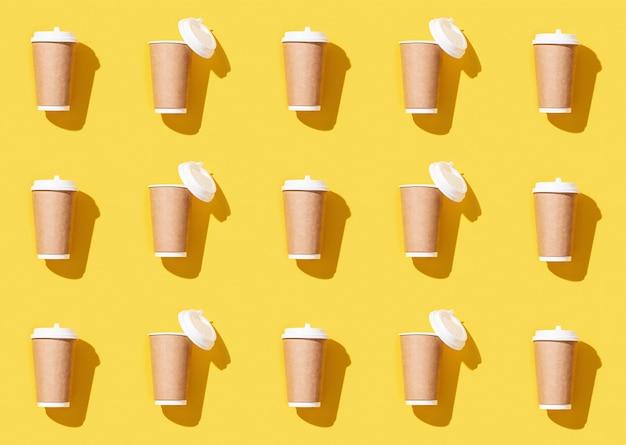 Patroonambacht neemt grote papieren beker weg voor koffie of drankjes, verpakkingssjabloon mock-up op geel.