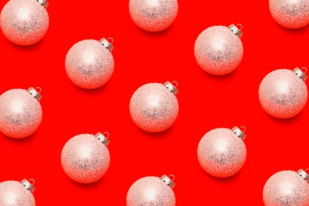 Patroonsamenstelling van witte kerstballen op rode achtergrond. platliggend, bovenaanzicht