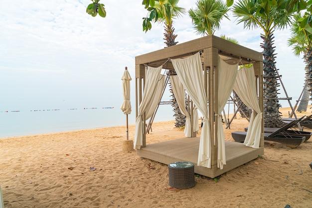 Paviljoen op strand met overzeese achtergrond in bewolkte dag - reis- en vakantieconcept
