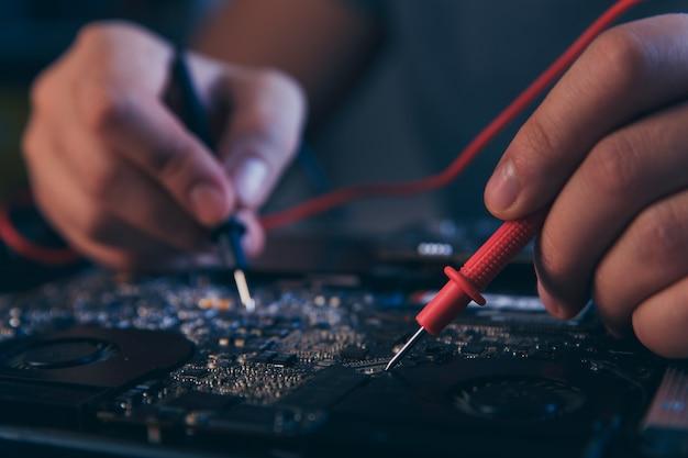 Pc-technologie. computerreparatiewerkplaats. ingenieur die laptoponderhoud uitvoert. hardwareontwikkelaar die elektronische componenten bevestigt.
