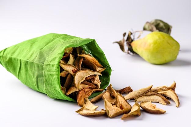 Pear chips in een katoenen zak en stukjes van deze vruchten