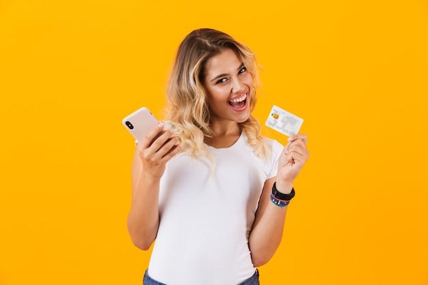 Peased vrouw met mobiele telefoon en creditcard in handen, geïsoleerd over gele muur