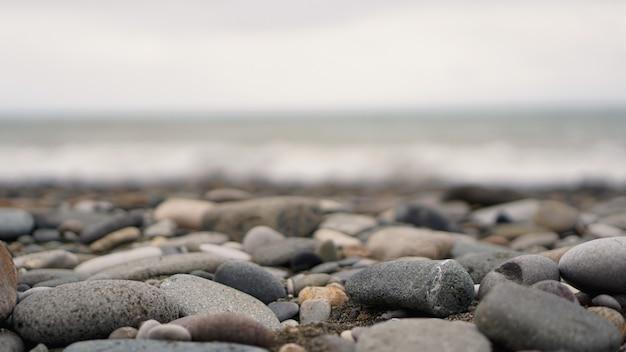 Pebble stenen aan de kust close-up in het wazige licht op de achtergrond in de verte. selectieve focus