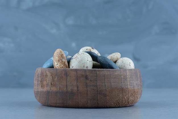 Pebble stenen snoepjes in een kom, op de marmeren tafel.