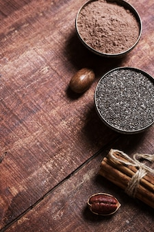 Pecannoten, chiazaden en cacao in kommen op een houten tafel