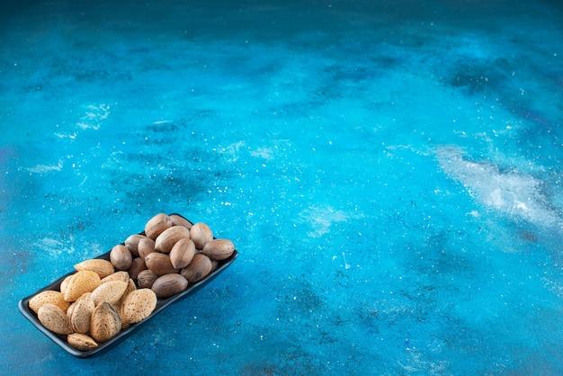 Pecannoten en amandelen in een kom, op de blauwe tafel.