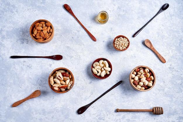Pecannoten, hazelnoten, amandelen, pijnboompitten, cashewnoten in houten kommen