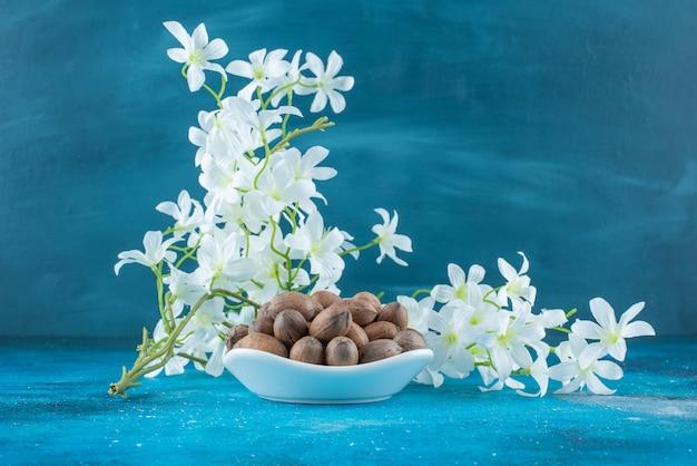 Pecannoten in een kom naast bloemen, op de blauwe tafel.