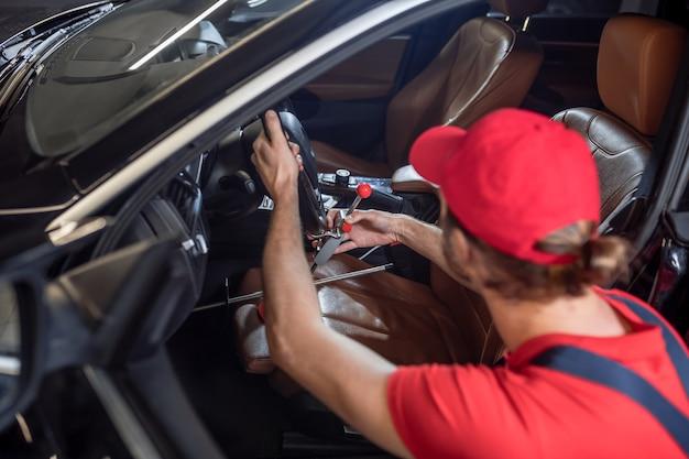 Pech reparatie. achteraanzicht van de mens in overall gehurkt in de buurt van bestuurdersstoel reparatie van autopech in garage