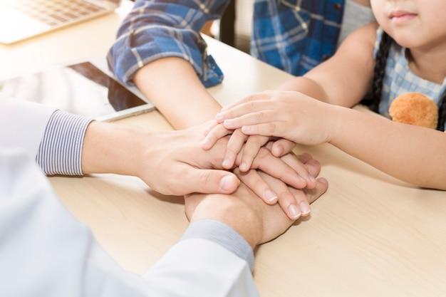 Pediater (arts) man handen samen, geruststellend en bespreken kind op een operatie