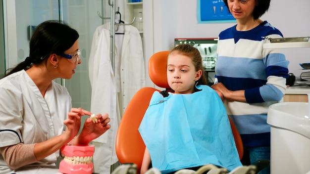 Pediatrische stomatoloog legt uit aan een kleine patiëntprocedure voor extractie met behulp van een model van tandheelkundige tanden. dokter met monster van menselijke kaak die informatie geeft voor het behouden van gezonde tanden, digitale xr