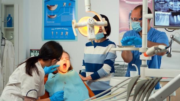 Pediatrische tandarts arts werkzaam in tandheelkundige unit met verpleegster en kleine meisje patiënt. stomatoloog spreekt met moeder van meisje met kiespijn zittend op stomatologische stoel terwijl man gereedschap voorbereidt.