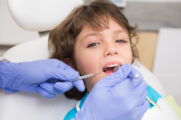 Pediatrische tandarts die kleine jongentanden onderzoeken als tandartsenvoorzitter