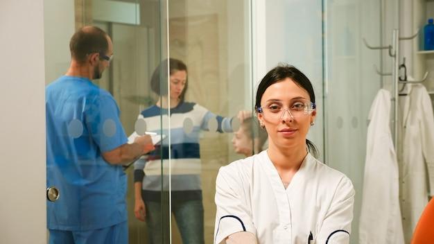Pediatrische tandarts die naar de camera kijkt terwijl hij glimlacht, terwijl de man assisteert en met patiënten spreekt over mondhygiëne op de achtergrond. stomatoloog zit voor de webcam en werkt in de tandheelkundekliniek