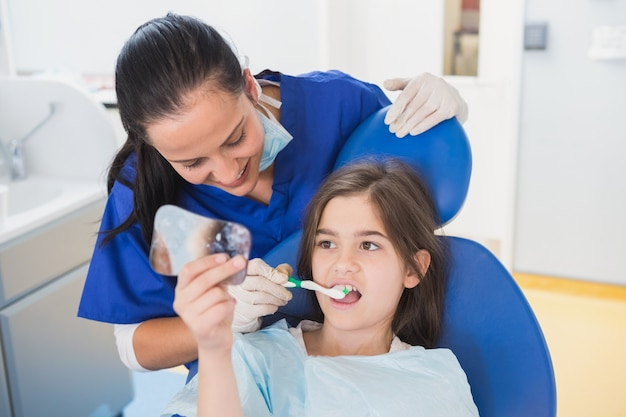 Pediatrische tandarts die tanden borstelt aan haar jonge patiënt