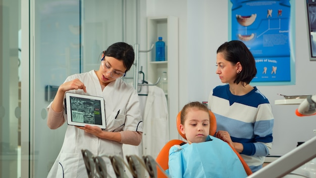 Pediatrische tandarts die tandenröntgenstraal op het computerscherm van tabletpc toont aan moeder van geduldig meisje bij tandkliniekkantoor. orthodontist die tablet gebruikt die tandheelkundige digitale radiografie aan vrouw uitlegt