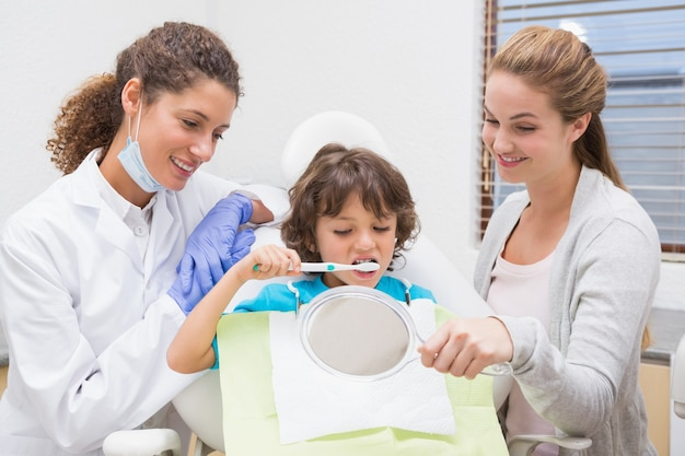 Pediatrische tandarts die weinig jongen toont hoe te tandenpoetsen met zijn moeder