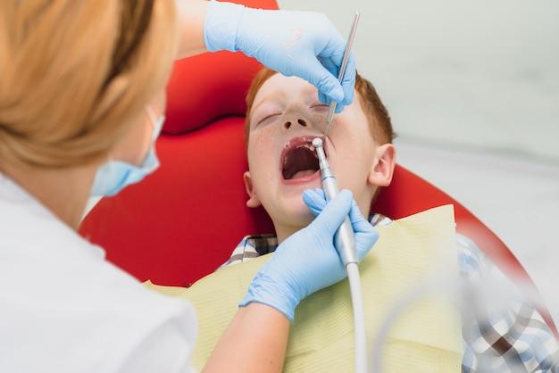 Pediatrische tandarts een kleine jongens tanden in de stoel van de tandarts te onderzoeken bij de tandheelkundige kliniek