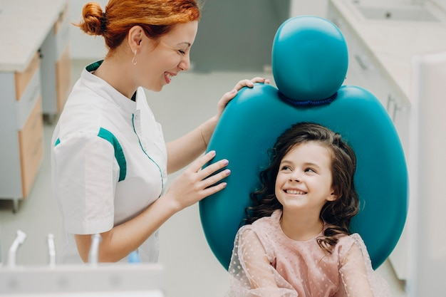 Pediatrische tandarts lachend kijken naar haar kleine patiënt. leuk meisje dat na tandonderzoek glimlacht.
