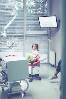 Pediatrische tandarts. meisje bij de receptie bij de tandarts.