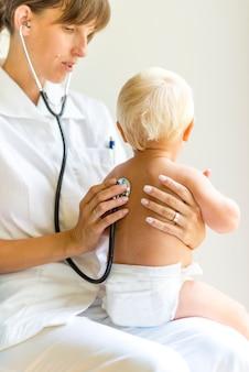 Pediatrische verpleegster die een baby onderzoekt