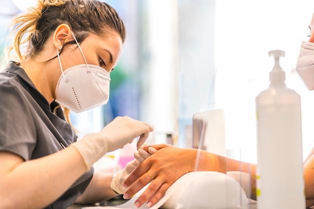 Pedicure behandeling, blonde werkster uit de manicure- en pedicuresalon met veiligheidsmaatregelen en gezichtsmaskers bij de heropening van de covid-19 pandemie. coronavirus