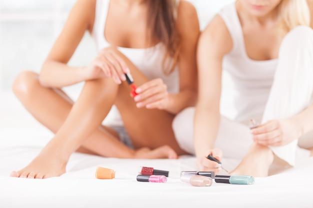 Pedicure. bijgesneden afbeelding van twee mooie jonge vrouwen die samen op bed zitten en pedicure doen