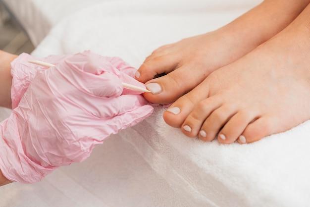Pedicure die beschermende handschoenen en voeten draagt