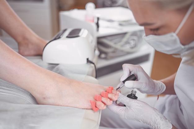Pedicure die witte nagellak op cliëntbenen doen die schellaklamp gebruiken