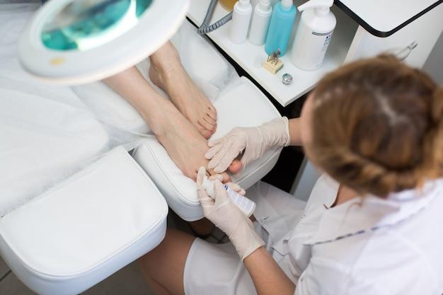 Pedicure dode huid remover voetrasp vrouw in nagelsalon. toepassing van de crème