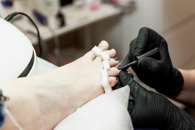 Pedicure in een schoonheidssalon. een gemaskerde vakman en zwarte handschoenen brengen nagellak aan. detailopname.