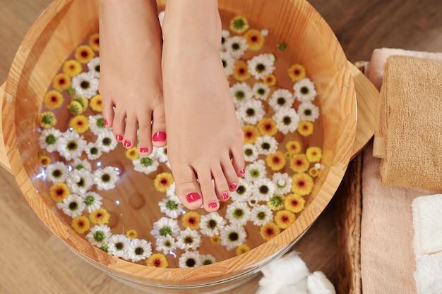 Pedicured voeten boven houten bassin