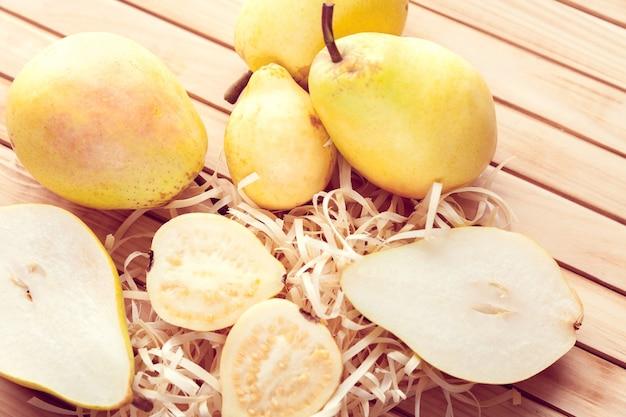 Peer en guave in tweeën gesneden op een houten oppervlak