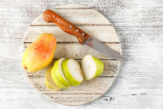 Peer en segmenten met mes bovenaanzicht op grungy en houten stuk achtergrond