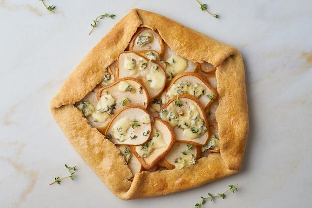 Peer galett met blauwe kaas, hartige taart, marmeren tafel, bovenaanzicht