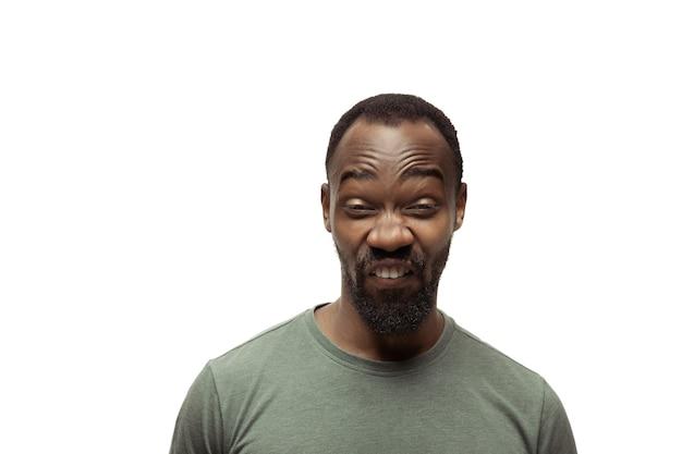 Peering jonge afro-amerikaanse man met grappige ongebruikelijke populaire emoties en gebaren