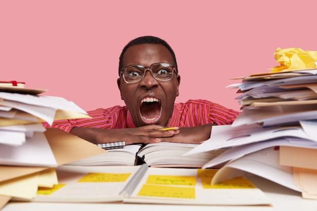 Peevish gekke mannelijke wetenschappelijke werker opent mond wijd, schreeuwt van woede, staart door stapels papieren, schrijft lijst op om te doen in notitieblok, draagt bril