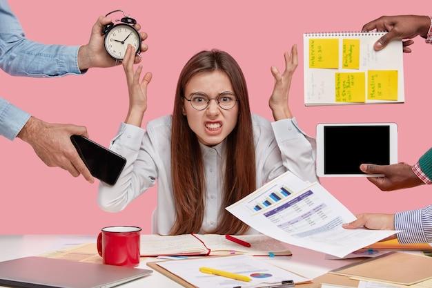 Peevish-vrouw houdt handen vol walging, wordt overweldigd door veel werk, voelt druk van collega's, zit achter de desktop met documentatie