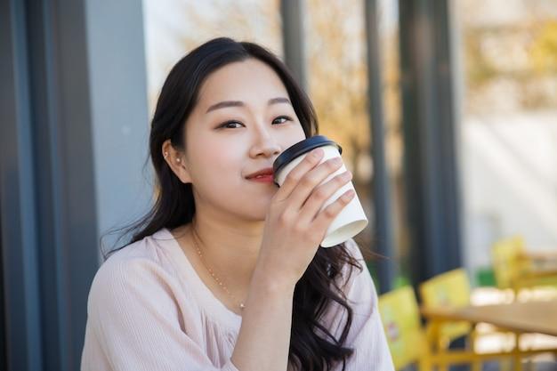 Peinzend aziatisch meisje die meeneemkoffie in straatkoffie genieten van