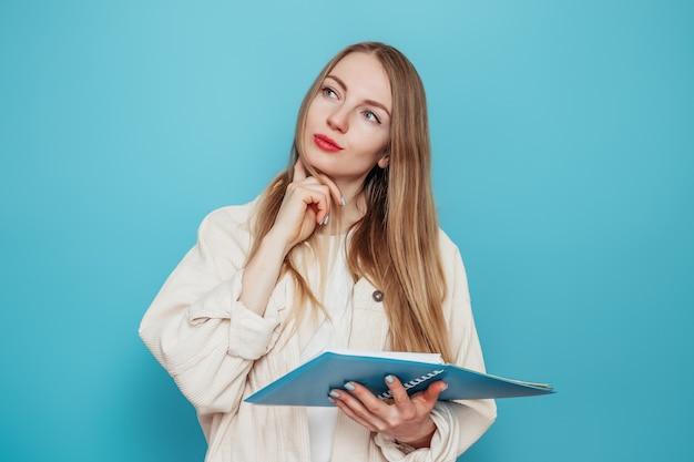 Peinzend blond studentenmeisje dat een open oefenboek houdt en ruimte zoekt die op blauwe muur wordt geïsoleerd.