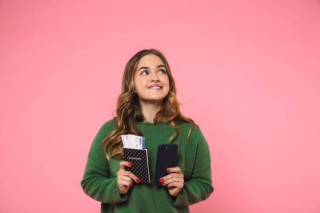 Peinzend glimlachend met paspoort met kaartjes en smartphone terwijl je omhoog kijkt over roze achtergrond