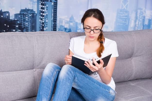 Peinzend meisje dat boek leest en een bril draagt, zittend op een bank in de woonkamer in een ontspannen sfeer