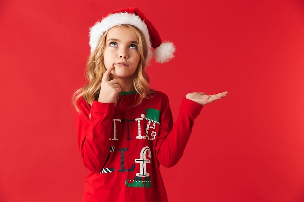 Peinzend meisje dat kerstmiskostuum draagt ?? dat zich geïsoleerd bevindt, exemplaarruimte voorstelt