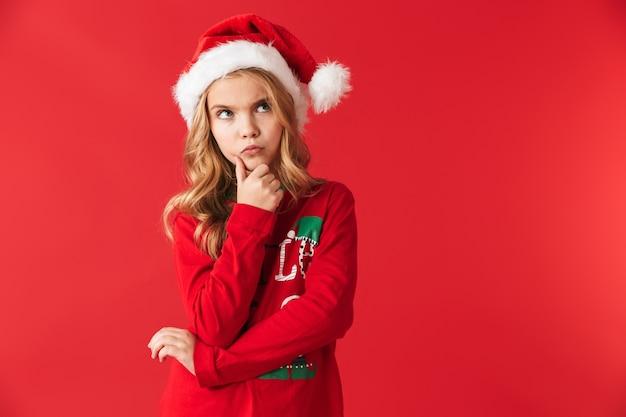 Peinzend meisje dat kerstmiskostuum draagt ?? status geïsoleerd