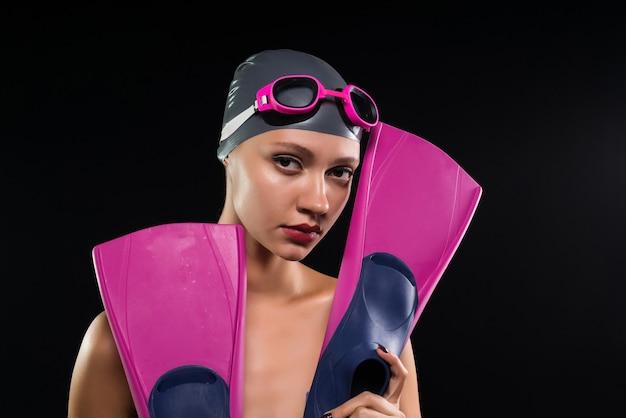 Peinzend meisje houdt flippers in de hand op zwarte achtergrond, zwembad, sport, zwemmen