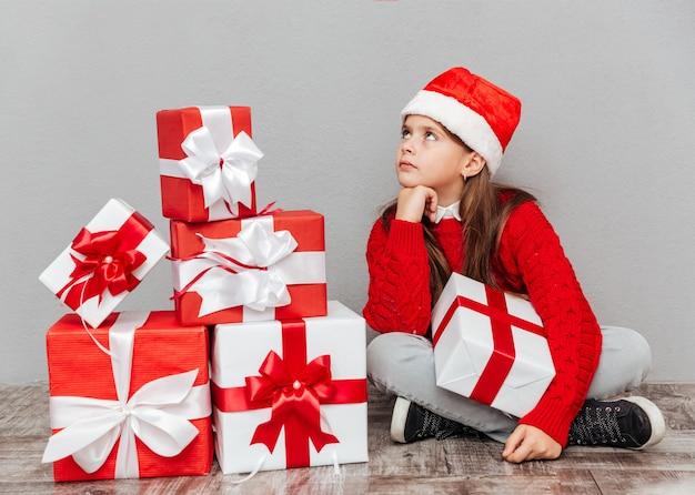 Peinzend meisje in kerstman hoed met huidige doos zitten en wachten