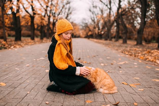 Peinzend sproetenmeisje die haar rood katje ter plaatse in de herfstpark aaien